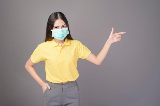 La mujer confidente joven en camisa amarilla está llevando la máscara quirúrgica sobre gris