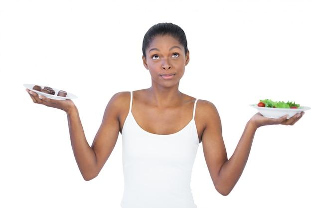 Mujer en conflicto decidiendo comer saludablemente o no