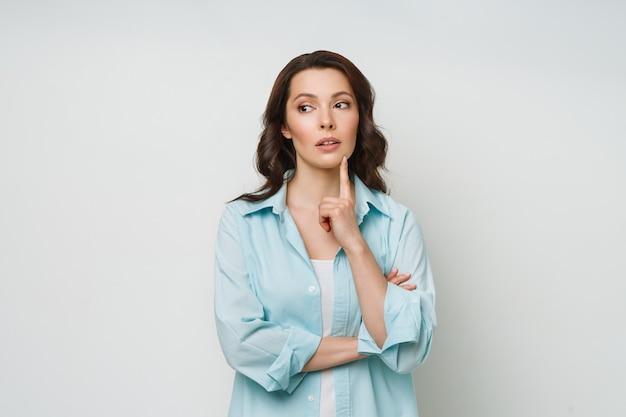 Una mujer confundida se para, insegura, se encoge de hombros y no puede dar una respuesta a una pregunta difícil.