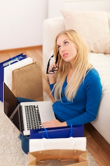 Mujer confundida con laptop y bolsas de compras