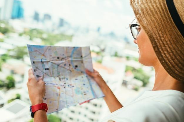 Mujer confundida con mapa de destino