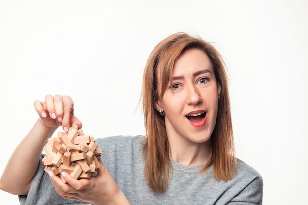 Mujer confundida con rompecabezas de madera.