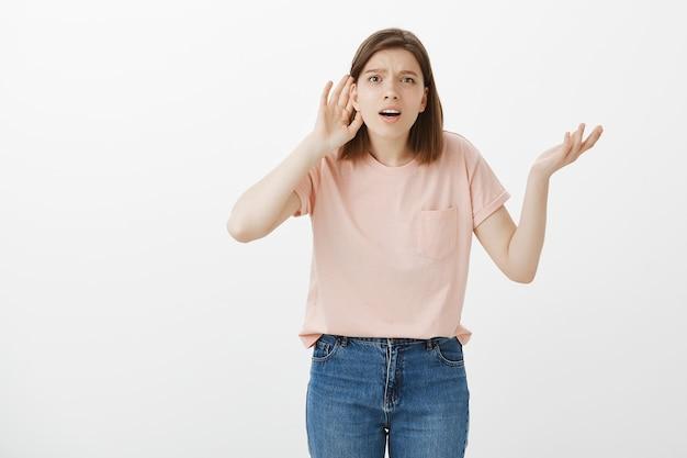 Mujer confundida tratando de escuchar a escondidas, no puede escuchar nada