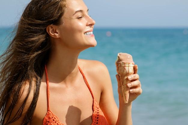 Mujer con cono de helado en la playa