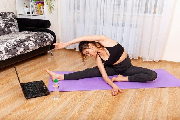 Mujer consciente meditar viendo tutorial de clase de yoga en línea en casa