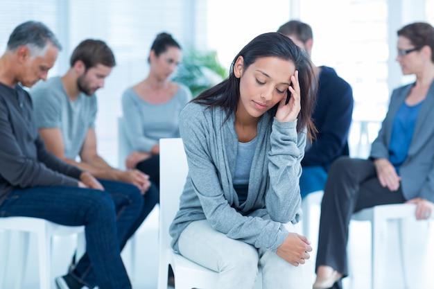 Mujer consolando a otro en grupo de rehabilitación en terapia