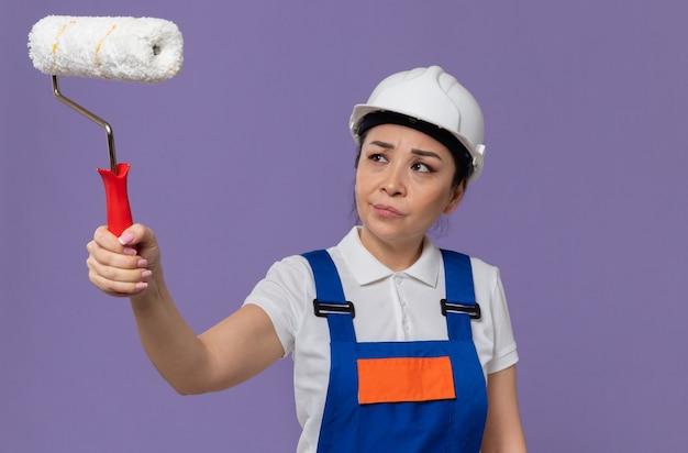 Mujer constructora asiática joven despistada con casco de seguridad blanco sosteniendo y mirando el rodillo de pintura