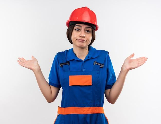 Mujer constructora joven confundida en uniforme extendiendo las manos aisladas en la pared blanca