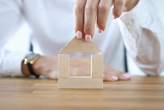 Mujer construir casa de cubos de madera en la mesa