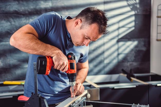 Mujer construyendo cocina y usando un taladro inalámbrico