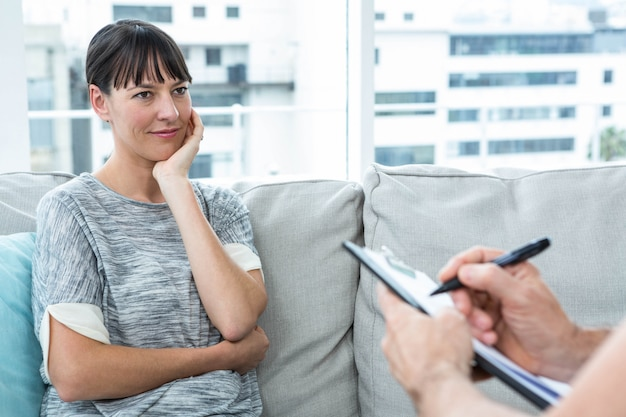 Mujer consultando a un terapeuta en la clínica y terapeuta escribiendo sus notas