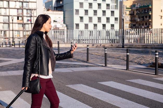 Mujer consultar teléfono mientras cruza la calle