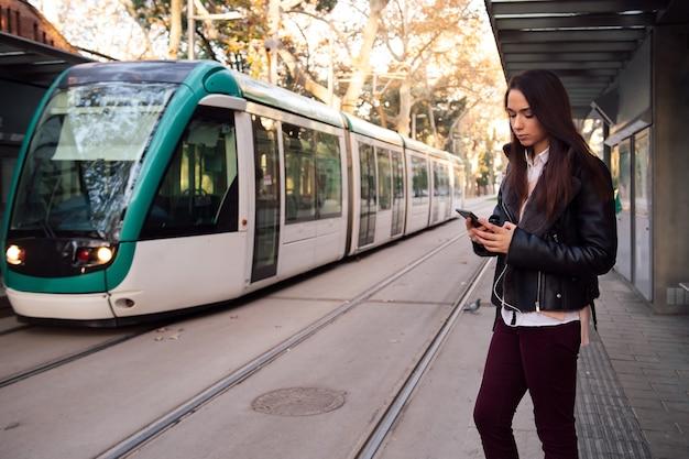 Mujer consultar teléfono en la parada del tranvía
