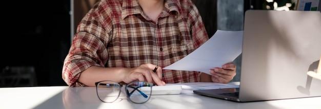 Mujer contable financiera que trabaja en la auditoría y calcula los gastos del informe anual financiero balance del balance, haciendo el documento de verificación de las finanzas y tomando notas en el papel del informe
