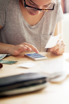 Mujer contando dinero en su teléfono