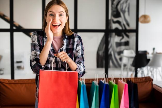 Mujer contando un secreto y sosteniendo una bolsa de papel