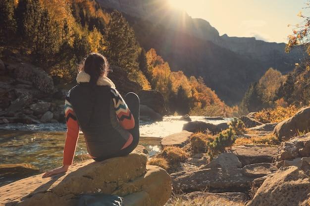Mujer contemplando la corriente de un río iluminado por la luz del sol entre las montañas. puesta de sol en el bosque en otoño. parque natural de ordesa y monte perdido en los pirineos
