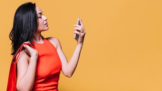 Mujer contemporánea con teléfono y bolso de compras.