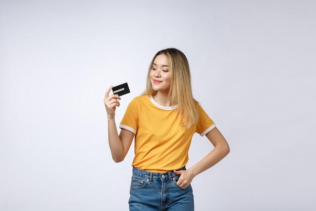 Mujer de contenido asiática sosteniendo fan de billetes de dólar de dinero y tarjeta de crédito