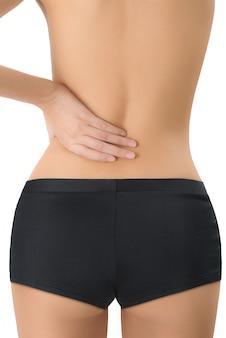Mujer conteniendo su espalda y masaje en el área del dolor aislado sobre fondo blanco.
