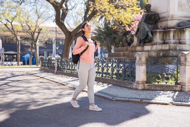 Mujer contenta con mochila y caminando por la ciudad