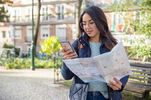 Mujer contenta que usa el mapa de papel y el teléfono inteligente al aire libre