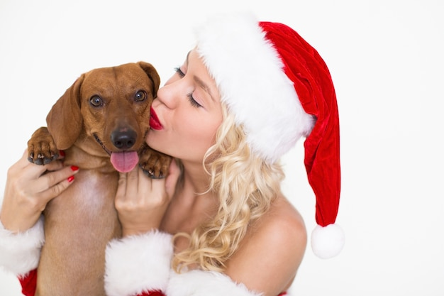 Mujer contenta en santa hat kissing cute dog