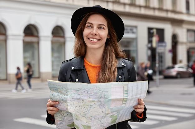 La mujer contenta sostiene un mapa de papel, visita la ciudad, mira a su alrededor, intenta encontrar un nuevo destino, usa un sombrero negro