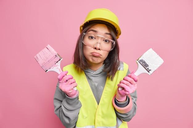 La mujer contratista sostiene dos pinceles para pintar en las manos, los labios, los labios, listos para pintar, las paredes interiores, usa casco de seguridad, lentes transparentes y uniforme