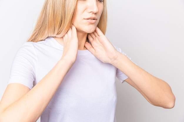 Mujer controlando la glándula tiroides por sí misma. cerca de mujer en camiseta blanca tocando el cuello con una mancha roja. el trastorno de la tiroides incluye bocio, hipertiroidismo, hipotiroidismo, tumor o cáncer. cuidado de la salud.