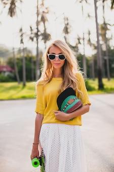 Mujer cool hipster con patineta y gorra posando sonriendo de vacaciones