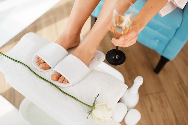 Mujer con copa de champán cerca del baño de pies, salón de belleza.