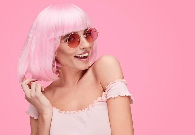 Mujer coqueta tocando el pelo rosa