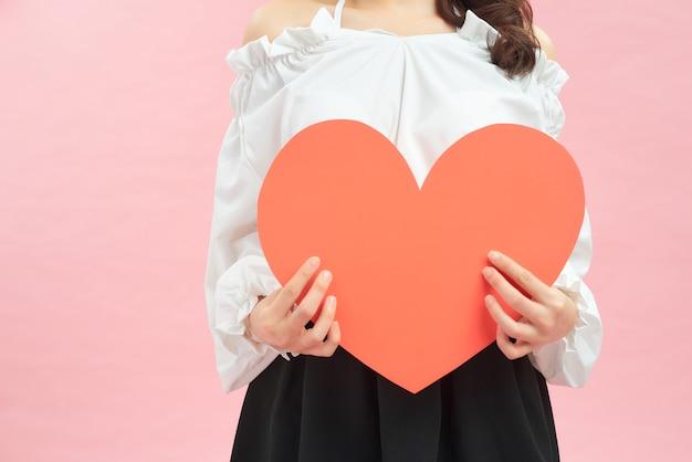 Mujer con corazón de papel rojo en sus manos