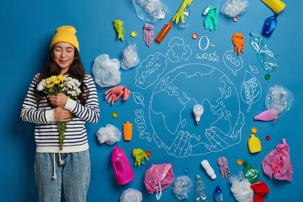Mujer coreana complacida satisfecha con el ramo, sostiene flores blancas y amarillas, se para contra el planeta dibujado y la basura plástica alrededor de la pared azul, limpia la naturaleza de la contaminación.