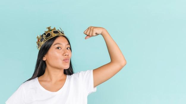 Mujer con corona y mostrando los músculos
