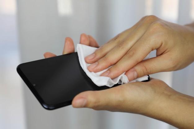 Mujer de coronavirus pandémico covid-19 que limpia con toallitas húmedas la pantalla del teléfono inteligente desinfecta contra el brote de la enfermedad de coronavirus 2019