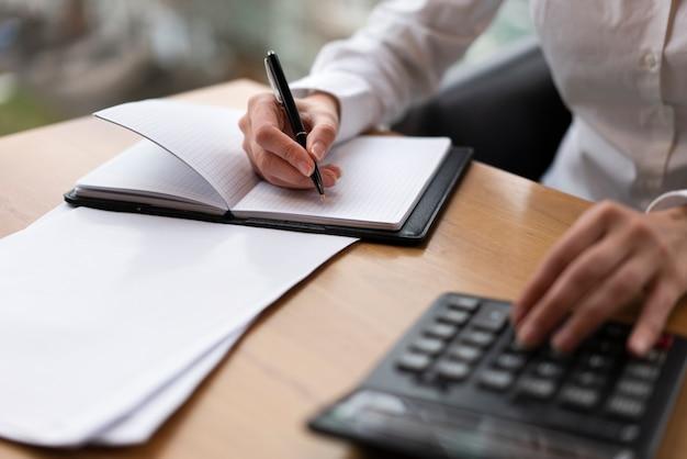 Mujer corporativa calculando y escribiendo