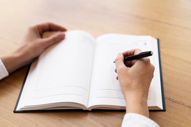 Mujer corporativa escribiendo en agenda