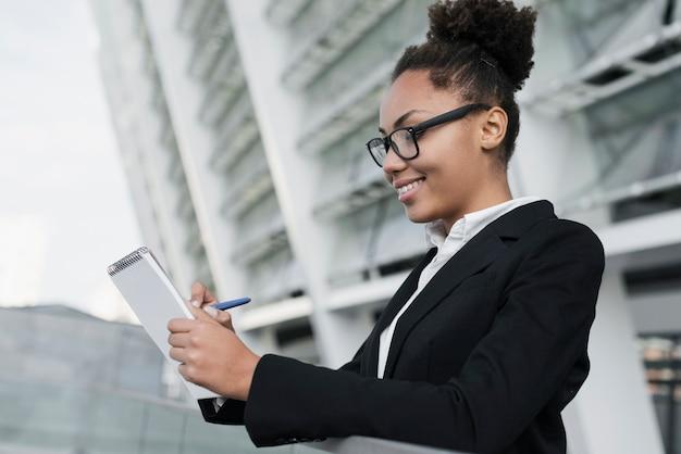 Mujer corporativa escribiendo en cuaderno
