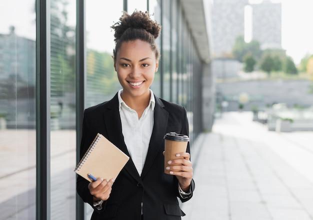 Mujer corporativa que sostiene el bloc de notas