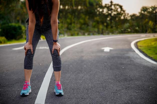 Mujer corredor atleta lesión de rodilla y dolor. mujer que sufre de rodilla dolorosa mientras se ejecuta.