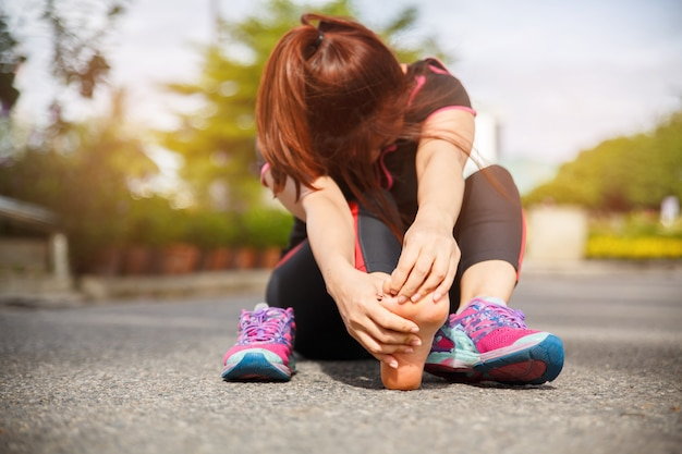 Mujer corredor atleta pie lesión y dolor. mujer que sufre de dolor en el pie mientras se ejecuta en la carretera.