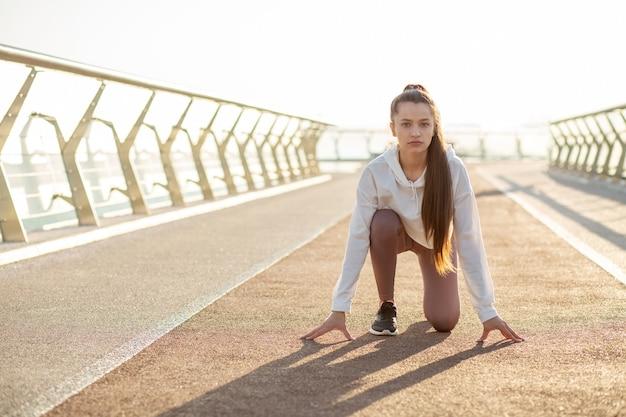 La mujer del corredor confiada en la posición inicial está lista para correr. espacio para texto