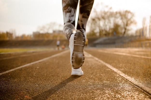 Mujer corredor corriendo en la pista en el estadio