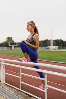 Mujer corredor estiramiento antes de maratón