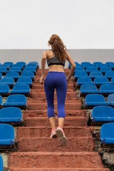 Mujer corredor haciendo escaleras en el estadio