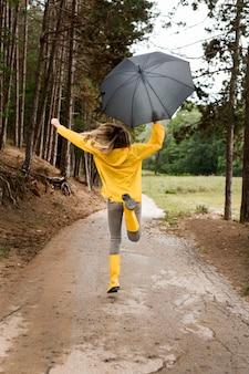 Mujer corriendo en el bosque mientras sostiene un paraguas