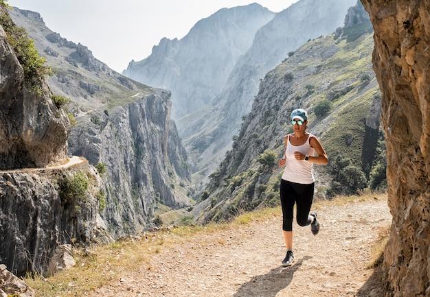 Mujer corriendo por el camino con gafas de sol en la ruta de los cuidados.