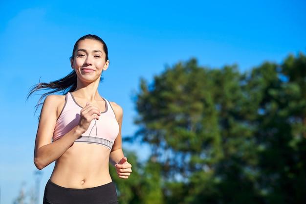 Mujer corriendo corredor femenino trotar durante el ejercicio al aire libre en un parque. hermosa chica en forma. modelo de fitness al aire libre. pérdida de peso